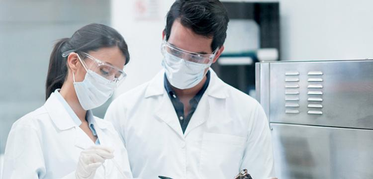 Man and woman wearing safety goggles and surgical masks