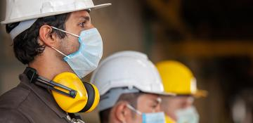 Line of 3 male workers in hard hats and masks